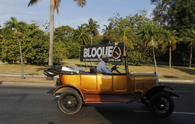 """A man drives his vintage car past a billboard with a message that reads in Spanish; """"Blockade, the longest genocide in history"""", in reference to the U.S. trade embargo imposed on Cuba, in Havana, Cuba, Friday, April 10, 2015. (Photo by Desmond Boylan/AP Photo)"""