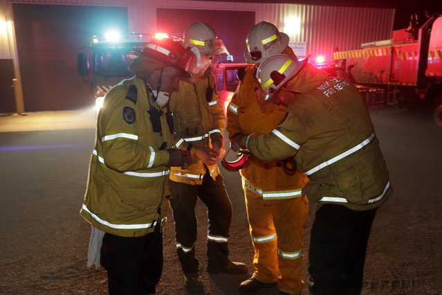 Firefighters at Burragate, Australia, gather outside the firehouse as they discuss a nearby fire threat Friday, January 10, 2020. Thousands of people are fleeing their homes and helicopters are dropping supplies to towns at risk of wildfires as hot, windy conditions threaten already fire-ravaged southeastern Australian communities. The danger is centered on Australia's most populous states, including coastal towns that lost homes in earlier fires. (Photo by Rick Rycroft/AP Photo)