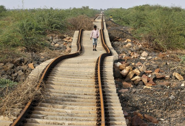 A villager walks on a railway track that was damaged after heavy monsoon rains near Patdi village in Gujarat, August 3, 2015. Dozens of people have been killed in the flood-like situation caused by torrential monsoon rains in some parts of the western Indian state of Gujarat, local media reported last week. (Photo by Amit Dave/Reuters)