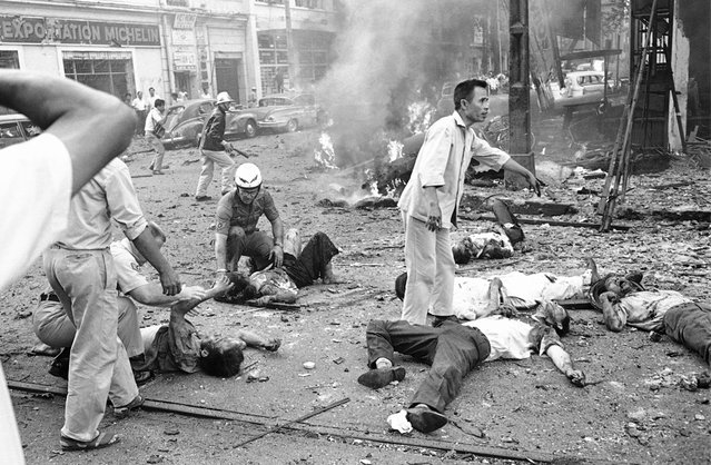 Injured Vietnamese receive aid as they lie on the street after a bomb explosion outside the U.S. Embassy in Saigon, Vietnam, March 30, 1965. Smoke rises from wreckage in background