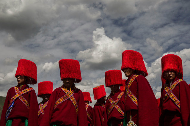 Ethnic Tibetans in traditional dress wait to perform on July 25, 2015 at a local government sponsored festival on the Tibetan Plateau in Yushu County, Qinghai, China. (Photo by Kevin Frayer/Getty Images)