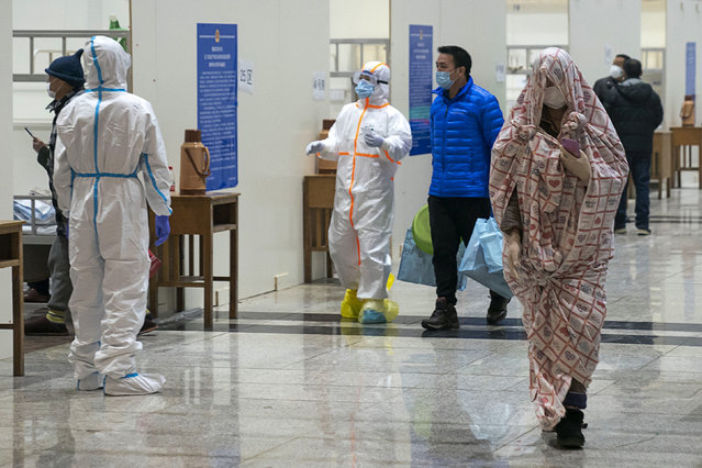 In this Wednesday, February 5, 2020, photo, medical workers in a protective suit help patients who diagnosed with the coronaviruses as they arrive at a temporary hospital which transformed from an exhibition center in Wuhan in central China's Hubei province. Ten more people were sickened with a new virus aboard one of two quarantined cruise ships with some 5,400 passengers and crew aboard, health officials in Japan said Thursday, as China reported 73 more deaths and announced that the first group of patients were expected to start taking a new antiviral drug. (Photo by Chinatopix via AP Photo)