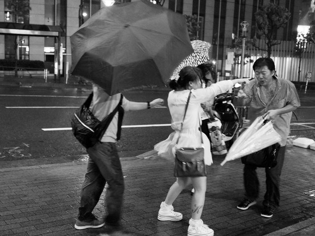 People walk against heavy rain and strong wind triggered by the Typhoon Guchol on June 19, 2012 in Meguro, Tokyo, Japan