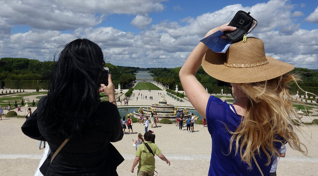 Tourists take pictures at the gardens of the Chateau de Versailles (Versailles Palace) in Versailles, near Paris, France July 30, 2017. (Photo by Stefano Rellandini/Reuters)