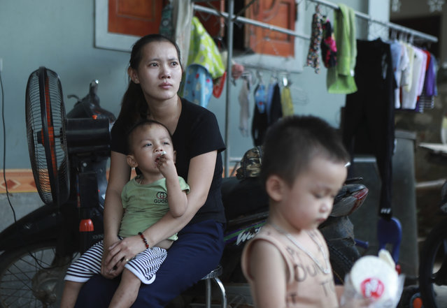 In this October 28, 2019, photo, Hoang Thi Nhiem, older sister of Hoang Van Tiep, who is feared to be among the England truck dead, holds her son in Dien Thinh village, Nghe An province, Vietnam. For many Vietnamese, a job in a Western European country is seen as a path to prosperity worth breaking the law for. But the risks of doing so are high and the consequences can be deadly, as the discovery of 39 bodies in a truck in England last week proved. (Photo by Hau Dinh/AP Photo)