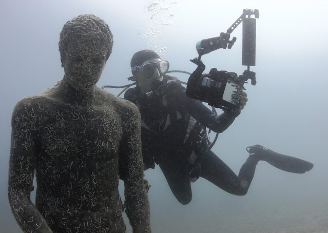 A diver takes a selfie with a replica of Apoxyomenos from the first or second century B.C. in Historical Underwater Park in Mali Losinj, Croatia, on Jule 24, 2014. (Photo by Antonio Bronic/Reuters)