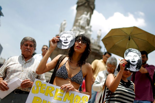 Demonstrators hold masks depicting Colombian citizen Mile Virginia, who was murdered along with photojournalist Ruben Espinosa and three other women, during a protest in Mexico City, August 16, 2015. Espinosa, a prominent Mexican news photographer was among five people found dead in a middle-class neighborhood of the capital on July 31, 2015. (Photo by Tomas Bravo/Reuters)