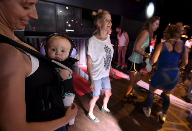 """A reveller dances with her child at """"Morning Gloryville"""" at the Ministry of Sound in south London August 11, 2015. (Photo by Toby Melville/Reuters)"""