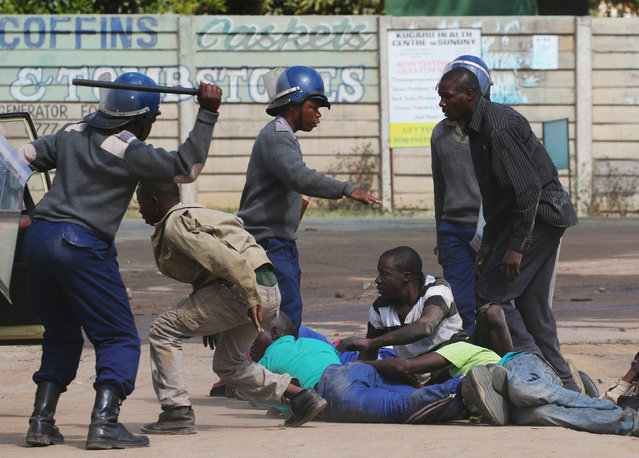 Riot police detain residents of Epworth suburb after a protest by taxi drivers turned violent in Harare, Zimbabwe, July 4, 2016. (Photo by Philimon Bulawayo/Reuters)