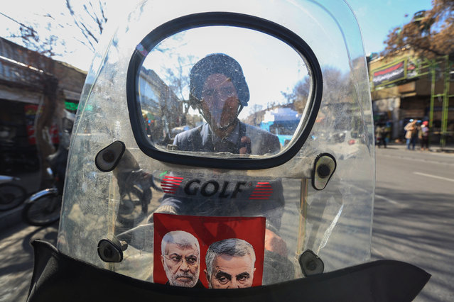 An Iranian man rides a scooter with a picture of late top Iranian general Qassem Soleimani and Iraqi paramilitary chief Abu Mahdi al-Muhandis, who were killed in a US drone strike near Baghdad's international airport, in the southern Tehran district of Molavi on February 9, 2020. In a country weighed down by sanctions, shaken by protests and stressed by military tensions with the United States, many Tehranis struggle to hide their pessimism. (Photo by Atta Kenare/AFP Photo)