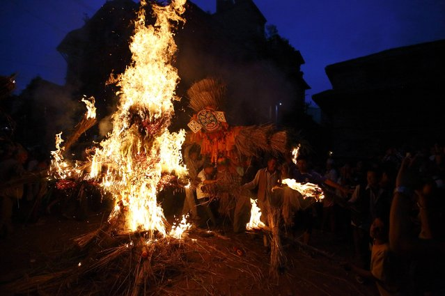 "People carry an effigy of the demon Ghantakarna, while another effigy of the demon is burnt to symbolize the destruction of evil, during the Ghantakarna festival in the ancient city of Bhaktapur July 25, 2014. According to local folklore, the demon is believed to ""steal"" children and women from their homes and localities. (Photo by Navesh Chitrakar/Reuters)"