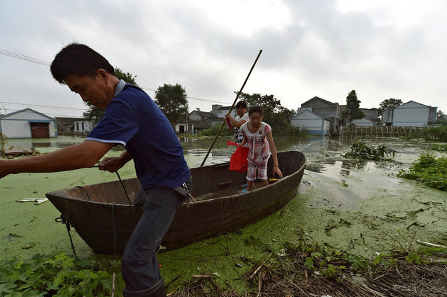 Residents make their way at a flooded area with a boat in Hefei, Anhui Province, China, July 9, 2016. (Photo by Reuters/Stringer)