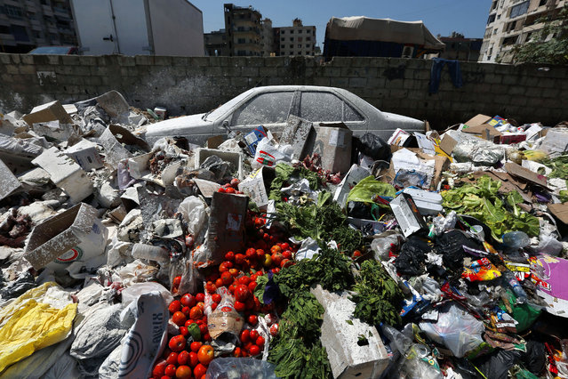 A car is seen between a pile of garbage covered with white pesticide in the Palestinian refugee camp of Sabra in Beirut, Lebanon, Thursday, July 23, 2015. The Lebanese cabinet has failed to agree on a solution for the country's growing garbage crisis, postponing discussion until next week as trash piles up on the streets. (Photo by Bilal Hussein/AP Photo)