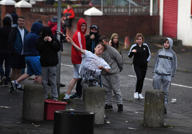 Nationalist youths throw bottles at police officers after the annual Orange march on July 12, 2016 in Belfast, Northern Ireland. The controversial Ardoyne interface is a flash point between the Catholic and Protestant communities with trouble flaring in the area frequently during the so called marching season. (Photo by Charles McQuillan/Getty Images)