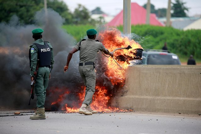 A police officer removes burning tires from the road, as protesters set up fires to block traffic along Airport Road in Abuja, Nigeria on September 4, 2019. (Photo by Afolabi Sotunde/Reuters)