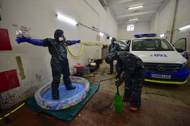 Volunteer workers of Search and Rescue (SAR) with special equipment, disinfect a volunteer while disinfecting police car at Local Police station to prevent the spread of coronavirus COVID-19, in Pamplona, northern Spain, Sunday, March 22, 2020. (Photo by Alvaro Barrientos/AP Photo)