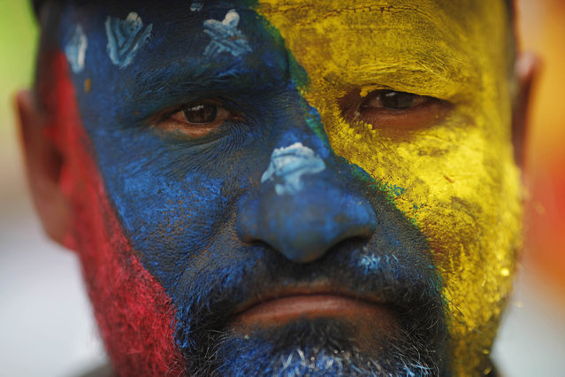 A supporter of Venezuela's acting President Nicolas Maduro stands with his face painted in the colors of his nation's flag outside the national electoral council where Maduro registers his candidacy for president to replace late President Hugo Chavez in Caracas, Venezuela, Monday, March 11, 2013. (Photo by Rodrigo Abd/AP Photo)