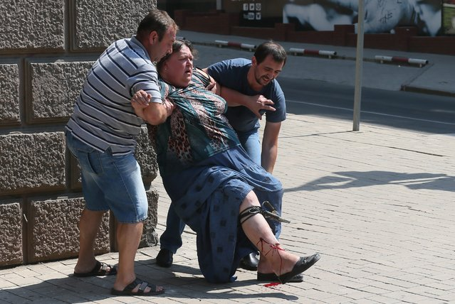 Local men help a wounded woman  after a mortar attack by the Ukrainian army of the center of Donetsk, Ukraine, 14 August 2014. Reports state that ten local people where wounded and one killed after the mortar attack. (Photo by Sergei Ilnitsky/EPA)