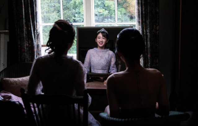 Debutante Annie Ding, 20 from Hong Kong, looks at her reflection in a mirror at Boughton Monchelsea Place ahead of the Queen Charlotte's Ball on September 9, 2017 in Maidstone, England. (Photo by Jack Taylor/Getty Images)