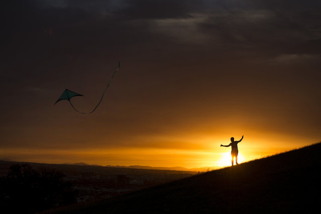 A youngster flies a kite at the sun sets at the Tio Pio park in Madrid, Monday, August 7, 2017. (Photo by Francisco Seco/AP Photo)