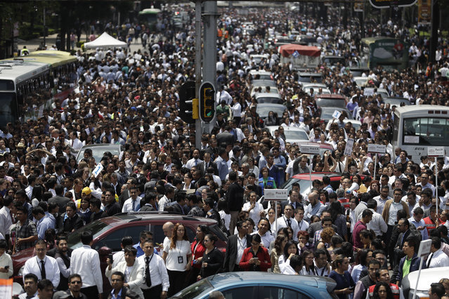 People evacuated from office buildings gather in Reforma Avenue after an earthquake in Mexico City, Tuesday September 19, 2017. (Photo by Rebecca Blackwell/AP Photo)