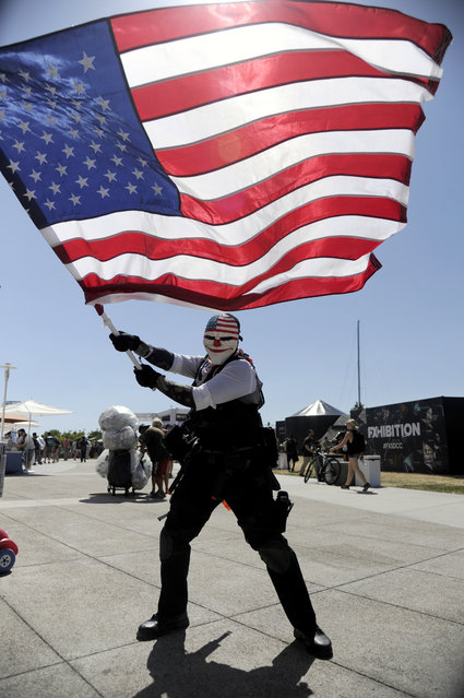 """Nicholas Prior, of San Diego, dressed as Dallas from the video game """"Payday: The Heist"""", waives an American flag on day 2 of Comic-Con International on Friday, July 22, 2016, in San Diego. (Photo by Chris Pizzello/Invision/AP Photo)"""