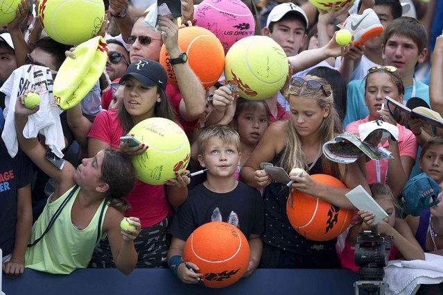 Children wait to get autographs from Roger Federer of Switzerland after he defeated Leonardo Mayer of Argentina in their first round match at the U.S. Open Championships tennis tournament in New York, September 1, 2015. (Photo by Carlo Allegri/Reuters)