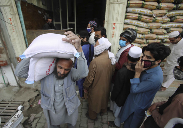 People buy sacks of flour fearing a shortage due to the coronavirus outbreak, in Peshawar, Pakistan, Tuesday, March 24, 2020. (Photo by Muhammad Sajjad/AP Photo)