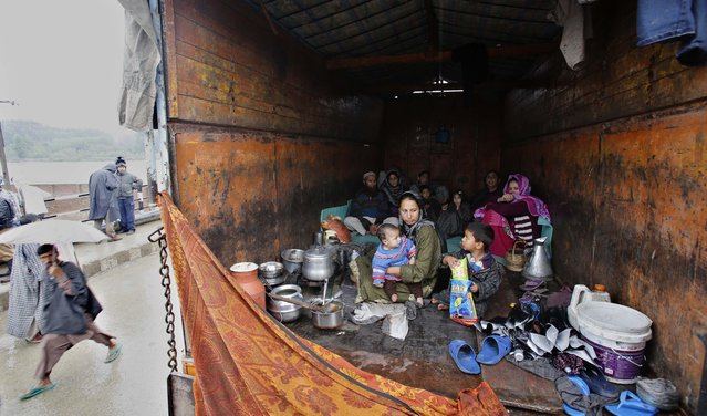 A Kashmiri family takes shelter inside a truck after their home was inundated by floodwaters in Srinagar, India, Saturday, September 6, 2014. Heavy monsoon rains have caused flash floods and landslides that left more than 100 people dead in the disputed Himalayan region of Kashmir and in eastern Pakistan, officials said Friday. (Photo by Mukhtar Khan/AP Photo)