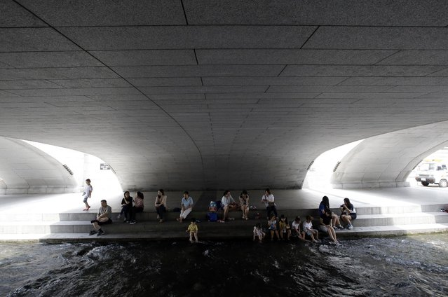 Visitors rest in the shade in the midday heat at Cheonggye stream in Seoul, South Korea, Tuesday, July 28, 2015. (Photo by Lee Jin-man/AP Photo)