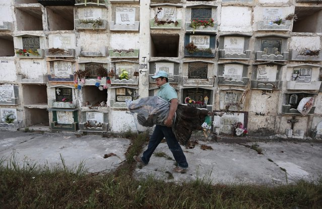 Grave cleaner Harold carries a mummified corpse at the Cemetery General in Guatemala City February 5, 2013.  If a lease on a grave has expired or not been paid, grave cleaners will break open the crypts to remove and rebury the bodies. Any remains that have not been claimed are packed into plastic bags, labeled and stored in mass graves. (Photo by Jorge Dan Lopez/Reuters)