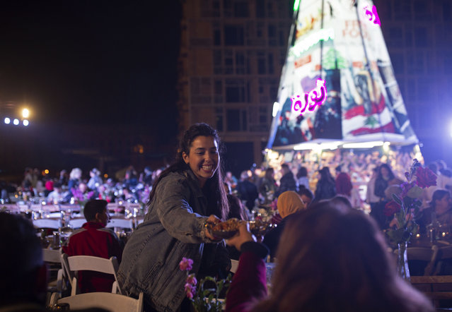 In this Monday, December 23, 2019, photo, a volunteer serves food at a public Christmas dinner, as an initiative to help those in need, in Martyrs Square where anti-government activists are encamped in Beirut, Lebanon. Lebanon is entering its third month of protests, the economic pinch is hurting everyone, and the government is paralyzed. So people are resorting to what they've done in previous crises: They rely on each other, not the state. (Photo by Maya Alleruzzo/AP Photo)