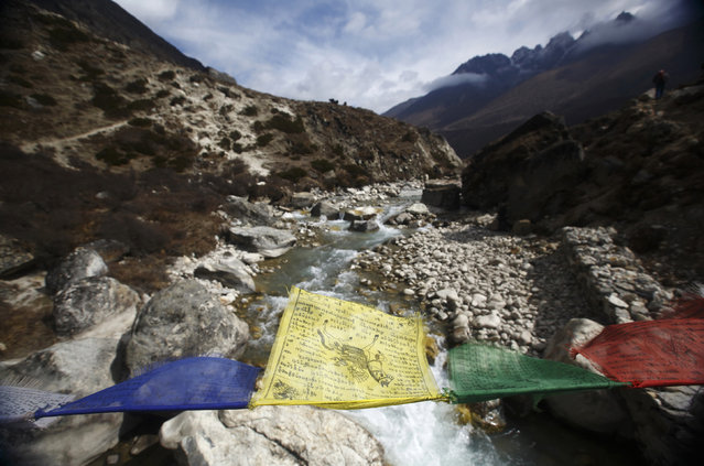 Prayer flags flutter over the Lobuche River on the way to Everest base camp near Pheriche, approximately 14107 feet above sea level, in Solukhumbu District May 3, 2014. (Photo by Navesh Chitrakar/Reuters)