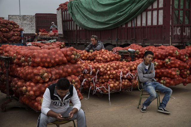 Chinese onion vendors wait for customers at a local market on September 26, 2014 in Beijing, China. (Photo by Kevin Frayer/Getty Images)