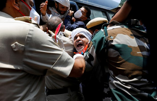 Police officers detain an activist from Swadeshi Jagran Manch, a wing of the Hindu nationalist organisation Rashtriya Swayamsevak Sangh (RSS), during a protest against China, in New Delhi, India on June 17, 2020. (Photo by Anushree Fadnavis/Reuters)