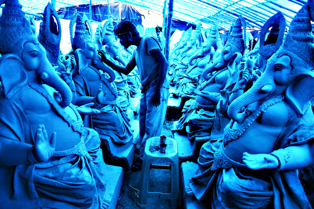 An Indian artist works on eco-friendly figures of Hindu God Lord Ganesh made with mud, jute and bamboo at a blue tarp-covered workshop on the outskirts of Hyderabad on September 15, 2015. The statues of eco-friendly clay Ganesh idols made with mud, jute and bamboo will reduce pollution during the Ganesh immersion. The popular eleven-day long Hindu religious festival, Ganesh Chaturthi will be celebrated from September 17-27 this year. (Photo by Noah Seelam/AFP Photo)