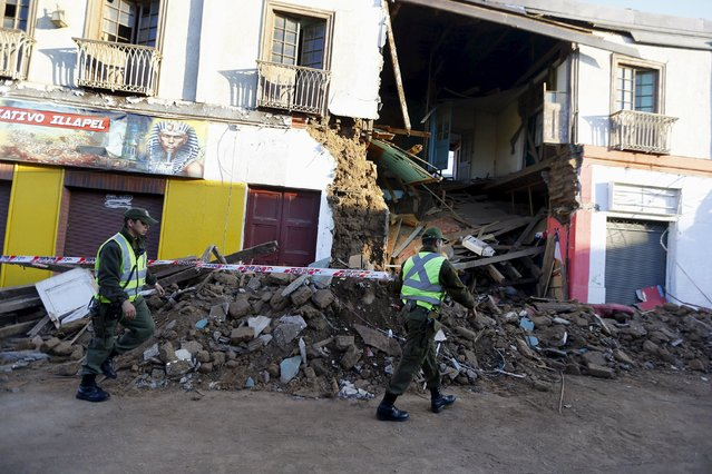 Police officers put barricade tape in front of a damaged building after an earthquake hit areas of central Chile, in Illapel town, north of Santiago, Chile, September 17, 2015. Strong aftershocks rippled through Chile on Thursday after a magnitude 8.3 earthquake that killed at least eight people and slammed powerful waves into coastal towns, forcing more than a million people from their homes. (Photo by Ivan Alvarado/Reuters)