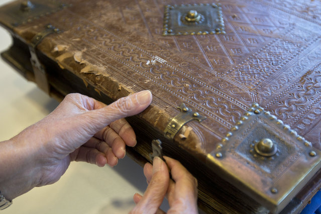 In this photo taken Sunday, October 5, 2014, a library official shows a 13th-century German prayer book containing the earliest evidence of the Yiddish language, at Israel's National Library in Jerusalem. (Photo by Sebastian Scheiner/AP Photo)