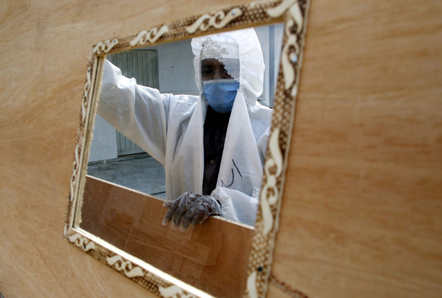 A worker wearing a face mask and a protective suit prepares coffins that are later distributed to hospitals to transport people who have died with the SARS-CoV-2 coronavirus that causes the pandemic COVID-19 disease in Islamabad, Pakistan, 07 June 2020. (Photo by Sohail Shahzad/EPA/EFE)