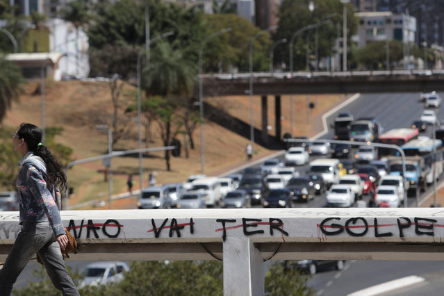 """A woman walks past a graffiti message that reads in Portuguese; """"There will be no coup"""" in reference to the country's political crisis, in Brasilia, Brazil, Friday, August 26, 2016. The second day of the impeachment trial of Brazil's suspended President Dilma Rousseff turned into a yelling match and was temporarily suspended on Friday after the head of Senate declared """"stupidity is endless"""" and sharply criticized a colleague who had questioned the body's moral authority. (Photo by Eraldo Peres/AP Photo)"""