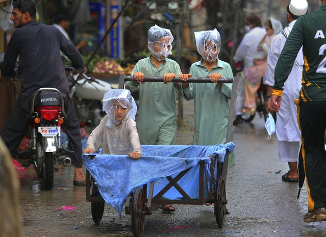 Youths cover their faces with plastic bags while pushing a handcart during rainfall in Peshawar, Pakistan, Sunday, July 12, 2020. (Photo by Muhammad Sajjad/AP Photo)