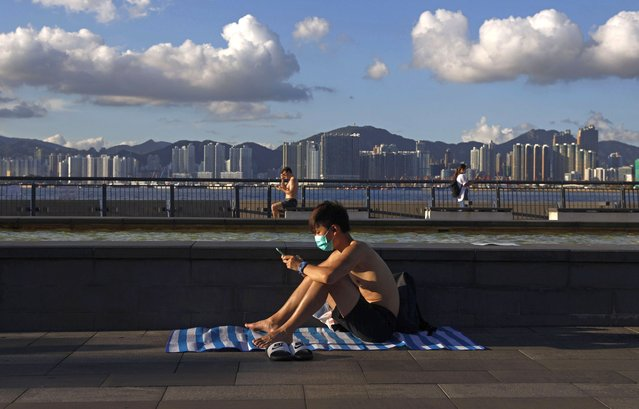 "A man wearing a face mask to protect against the new coronavirus sits in the sun at a park in Hong Kong, Wednesday, July 22, 2020. Hong Kong is facing a ""critical stage"" in its fight against COVID-19, and the government is extending anti-virus measures, Health Secretary Sophia Chan said Wednesday. Hong Kong has made it mandatory to wear masks on public transport, in indoor areas and passenger terminals. (Photo by Kin Cheung/AP Photo)"