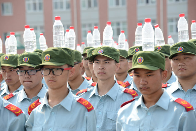 Freshmen in Zhengzhou Institute of Aeronautical Industry Management head bottles of mineral water for upright stand during military training on September 17, 2015 in Zhengzhou, Henan Province of China. More than 6,800 freshmen in the school are required to take part in the military training. (Photo by ChinaFotoPress/ChinaFotoPress via Getty Images)