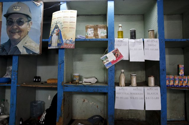 """A photograph of Cuba's President Raul Castro hangs next to samples of basic products like rice, sugar and oil that are on sale at a subsidised state store, or """"bodega"""", where Cubans can buy with a ration book they receive annually from the government in Havana September 18, 2015. (Photo by Carlos Garcia Rawlins/Reuters)"""