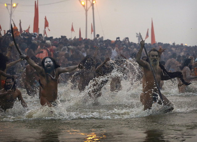 Indian Hindu holy men, or Naga Sadhus, run naked into the water at Sangam, the confluence of the Ganges, Yamuna and mythical Saraswati river, during the royal bath on Makar Sankranti at the start of the Maha Kumbh Mela in Allahabad, India, Monday, Jan. 14, 2013. Millions of Hindu pilgrims are expected to take part in the large religious congregation that lasts more than 50 days on the banks of Sangam which falls every 12 years. (Photo by Kevin Frayer/AP Photo)