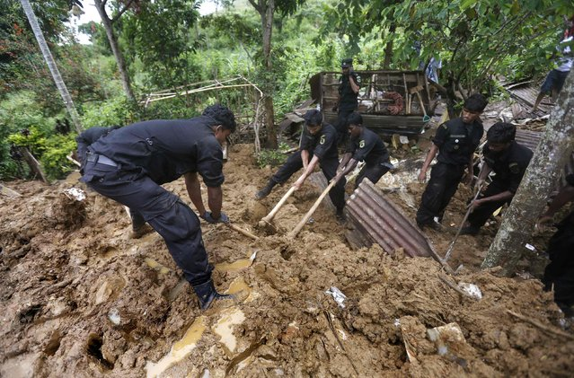 Rescue team members conduct a search at the site of a landslide at the Koslanda tea plantation near Haldummulla October 30, 2014. (Photo by Dinuka Liyanawatte/Reuters)