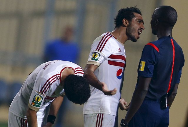 Mahmoud Kahraba (C) of Egypt's Zamalek argues with Gambian referee Bakary Papa Gassama (R) after the end of their Confederation Cup semi-final soccer match against Tunisia's Etoile du Sahel at Petro Sport stadium in Cairo, Egypt, October 3, 2015. (Photo by Amr Abdallah Dalsh/Reuters)