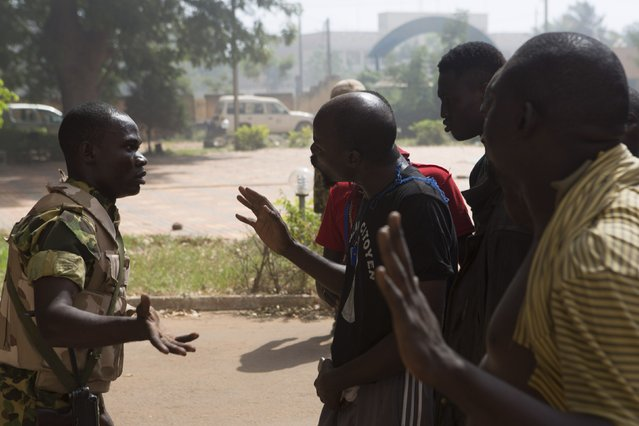 Anti-government protesters speak with a soldier outside the state TV building in Ouagadougou, capital of Burkina Faso, October 30, 2014. Tens of thousands of protesters demanding the ousting of Burkina Faso's veteran President Blaise Compaore faced off with security forces outside the presidential palace after burning parliament and ransacking state television on Thursday. (Photo by Joe Penney/Reuters)