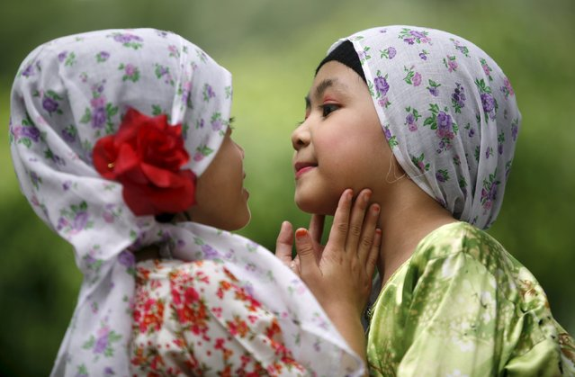 Nur Insyirah Mohd Halim (R), a Muslim girl in a Malay traditional dress, asks her classmate, Maisarah Abdul Aziz, 6, to check her lipstick before their performance during the carnival marking the United Nations Universal Children's Day, in Shah Alam outside Kuala Lumpur in this November 22, 2009 file photo. (Photo by Bazuki Muhammad/Reuters)
