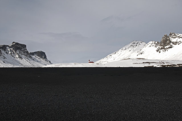 """""""Iceland Chapel"""". A red roofed chapel surrounded by snow covered mountains in Vik, Iceland. The foreground is volcanic black sand. Photo location: Vik, Iceland. (Photo and caption by Adrian Brown/National Geographic Photo Contest)"""